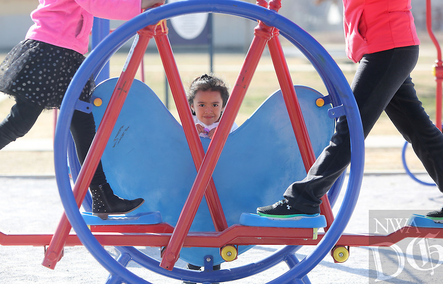 NWA Democrat-Gazette/DAVID GOTTSCHALK   Isabell Barroso, 4, looks through the exercise equipment Wednesday, February 8, 2017, that Evanyela (cq) Barroso, 9, and Sandra Perez are using in at Luther George Grove Park in Springdale.  The outside exercise equipment was provided as the result of a joint use agreement grant through the partnership between the city and the Springdale School District.
