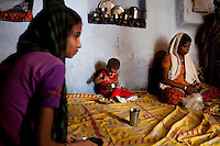 Sadma Khan (left, in purple), 19, rests with her 18 month old son and mother (right) in her mother's one-room house that they share with her brothers and sister in a slum area of Tonk, Rajasthan, India, on 19th June 2012. She was married at 17 years old to Waseem Khan, also underaged at the time of their wedding. The couple have an 18 month old baby and Sadma is now 3 months pregnant with her 2nd child and plans to use contraceptives after this pregnancy. She lives with her mother since Waseem works in another district and she can't take care of her children on her own. Photo by Suzanne Lee for Save The Children UK