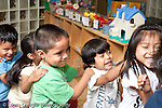 Education Preschool 3-5 year olds group of children boy and girls holding each other's shoulders in a line circle time activity laughing boy shorter than his peers horizontal New York City