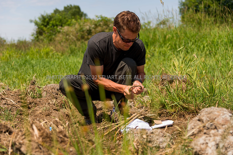 6/22/2015 &mdash; Everett, WA, USA<br /> <br /> Steven Rinella, an avid outdoorsman and hunter, prepares to cook both wild duck and domesticated chicken over an open wood fire in Everett, WASH. <br /> <br /> Here he gathers branches and lays them out to help start the fire.<br /> <br /> Both birds were skewered with branches cut from nearby Alder trees and hung over the fire using more Alder branches.<br /> <br /> <br /> Photograph by Stuart Isett<br /> &copy;2015 Stuart Isett. All rights reserved.