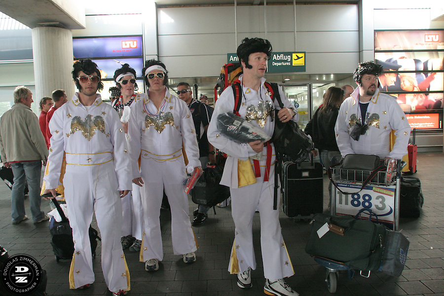 """USA National Soccer Team fans, (left to right) Billy Ryan of Kansas City, MO, Barry Ryan of Kansas City, MO, Chris Widmer of Columbia, MO, Pat Ryan of Kansas City, MO, and Philippe Lechevin of Kansas City, MO, dressed up in flight suits as the American Icon Elvis, look for transportation to the airport train station after exiting customs at Düsseldorf Airport. The group was traveling by train to Cologne, Germany and their hotel. They arrived at Düsseldorf Airport in Germany on Saturday morning, June 10th, 2006 after an overnight flight from JFK airport in New York City.  The fans were part of a tour group arraigned by Pat Ryan from Kansas City, MO called """"2006 World Cup Trip."""" They were among the thousands of American fans who have descended on Germany to support the USA National team during the 2006 FIFA World Cup. The first game for the USA is against the Czech Republic in Gelsenkirchen on Monday June 12th."""