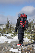 Hiker along the Mt Parker Trail, near the summit of Mount Resolution, in the White Mountains, New Hampshire USA.