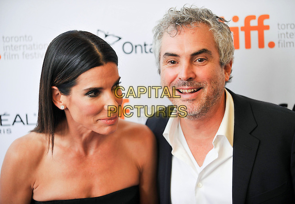 Sandra Bullock &amp; Alfonso Cuaron<br /> &quot;Gravity&quot; Premiere - 2013 Toronto International Film Festival held at Princess of Wales Theatre<br /> September 8th, 2013<br /> TIFF headshot portrait black strapless suit jacket white shirt stubble facial hair<br /> CAP/ADM/BPC<br /> &copy;Brent Perniac/AdMedia/Capital Pictures