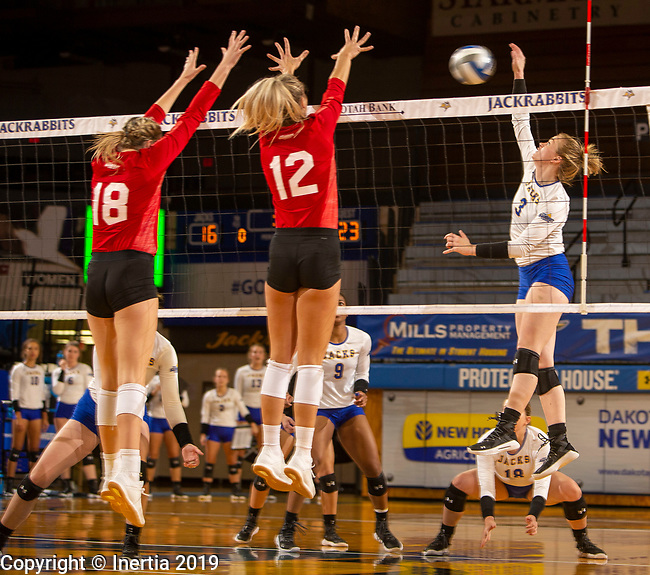 BROOKINGS, SD - OCTOBER 8: Makenzie Hennen #3 from South Dakota State University looks to get a kill past Maddie Wiedenfeld #18 and Elizabeth Loschen #12 from the University of South Dakota during their match Tuesday evening at Frost Arena in Brookings. (Photo by Dave Eggen/Inertia)