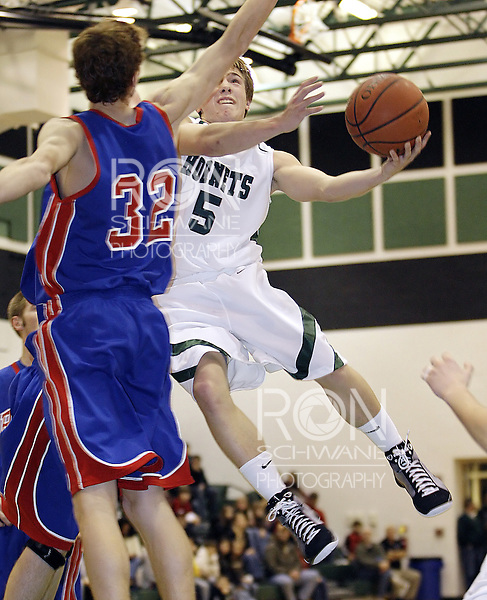 Highland's John Alexander puts up a shot around Revere's Andy Trem during the second quarter. (Photo by Ron Schwane)