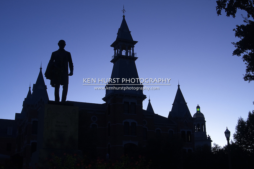 Statue of Rufus C. Burleson, towers and parapets of Old Main building and Pat Neff Hall at Baylor University, Waco, Texas in silhouette at sunset.