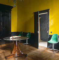 Green retro chairs combine with an antique table in a small room with walls painted an unconventional yellow lacquer