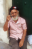 Elderly man with full beard sitting in doorway smoking pipe,