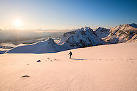 Female hiker descending snowy hillside from summit or Ryten, Moskenesøy, Lofoten Islands, Norway