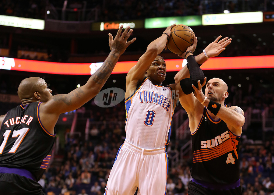 Feb. 10, 2013; Phoenix, AZ, USA: Oklahoma City Thunder guard Russell Westbrook (0) drives to the basket against Phoenix Suns center Marcin Gortat (4) in the first quarter at the US Airways Center. Mandatory Credit: Mark J. Rebilas-
