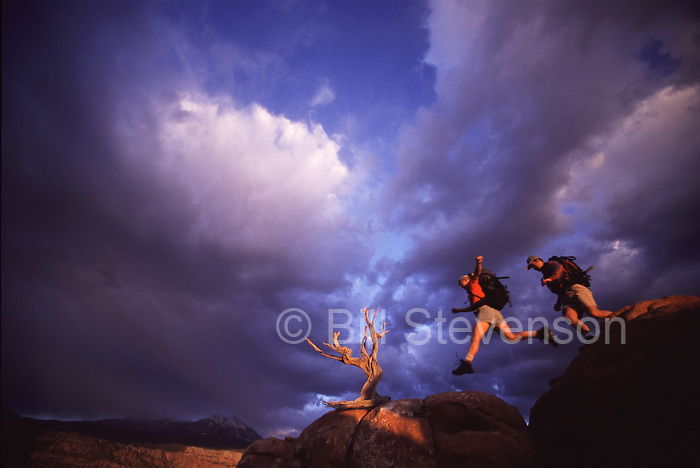 A picture of a couple jumping over rocks with dramatic clouds behind near Moab, Ut.