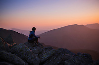 Female hiker watches sunset over mountains from summit of Glyder Fach, Snowdonia national park, Wales