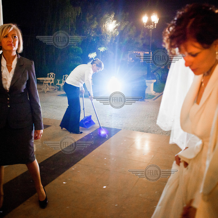 A member of staff sweeps the floor while the bride dances during a reception at the Venecia Palace Hotel. The hotel was built in 2008 by Polish businessman Waclaw Gozlinski, who concluded that potential guests, exposed to a diet of American B movies and television soap operas, have developed a taste for kitch for their parties and weddings. As Poles are getting richer, the hotel is now the most popular wedding party venue in Poland and needs to be booked over a year in advance.