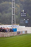 Home team supporters watching the second-half action at the Harry Williams Riverside Stadium, home to Ramsbottom United as they played Barwell in a Northern Premier League premier division match. This was the club's 13th league game of the season and they were still to record their first victory following a 3-1 defeat, watched by a crowd of 176. Rams bottom United were formed by Harry Williams, the current chairman, in 1966 and progressed from local amateur football  in Bury to the semi-professional leagues.