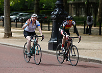 16th May 2020, London, England;  Cyclists cycling towards Buckingham Palace on the mall while not wearing gloves or a mask while on of them waves to the photographer