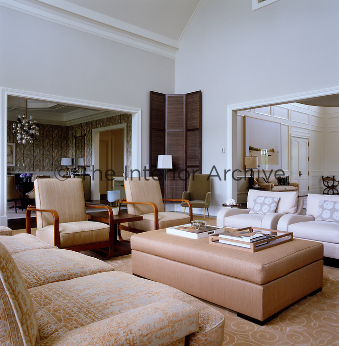 The contemporary double-height living room is furnished with a mixture of contemporary and vintage pieces upholstered in a neutral palette