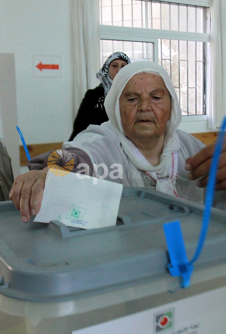 A Palestinian woman casts his vote for the municipal elections at a polling station in the West Bank village of of Deir al-Ghusun north of Tulkarm, on October 20, 2012. Palestinians in the West Bank voted in local elections in what was the first time they had gone to the polls since 2006. Photo by Nedal Eshtayah