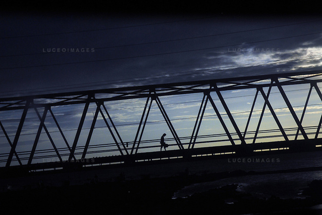 A construction worker walks across a bridge outside of Manila, Philippines..**For more information contact Kevin German at kevin@kevingerman.com