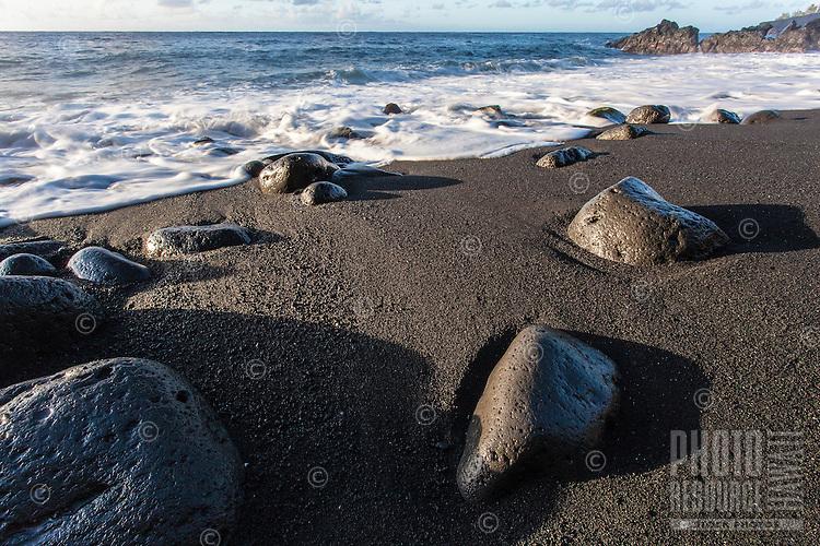 oamy waves flowing onto rocks and black sand at Kehena Beach, Pahoa, Big Island.