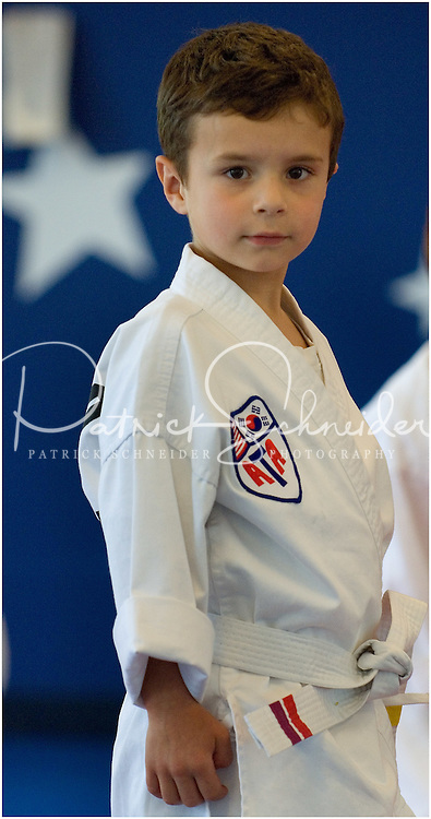 A young boy (model released) practices the art of Tae Kwan Do, a sport he was just beginning to learn, as shown by the white belt, which signifies beginner.