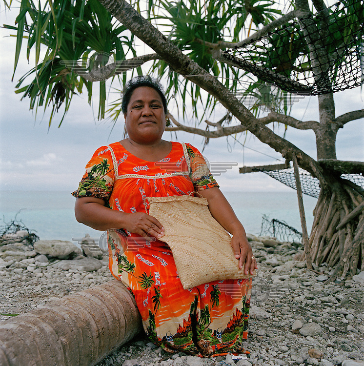 A women sits on the edge of the lagoon with a handmade bag she has finished making from the dried and pounded leaves of the pandanus tree.