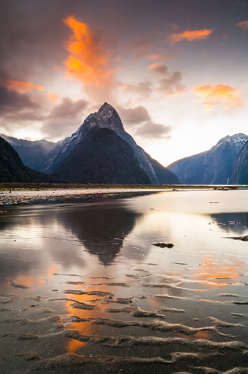 Sunset light in clouds over Mitre Peak is reflected in the rippled sand at low tide. Milford Sound, Fiordland National Park, South Island, New Zealand. Stock photo, canvas, fine art print