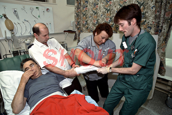 Manipulation of colles fracture. Colles back slab being applied. The male nurse is applying counter traction, the doctor is appling traction and manipultion whilst the female nurse is plastering.
