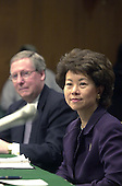 Washington, DC - January 24, 2001 -- Elaine Chao, U.S. Secretary of Labor-designate, right, listens to the Senator's opening remarks during her confirmation hearing before the U.S. Senate Health, Education, Labor and Pensions Committee.  Her husband, U.S. Senator Mitch McConnell (R-Kentucky), left, looks on.<br /> Credit: Ron Sachs / CNP