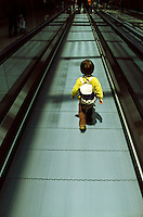 A young boy wearing a small backpack walks alone along along a moving walkway at Narita Airport in Tokyo, Japan. May 2005