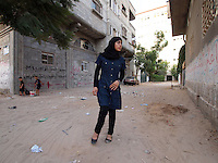 "Amira Al-Qerem (16) walks, with some difficulty from the injury to her right leg, in her old neighbourhood in Gaza City on October 27 2010. Amira was missing and presumed dead after she was injured by one of the same explosions that killed her father, brother and sister during the last days of the Israeli invasion of Gaza in 2009. She was found three days later, after her family thought they had buried her remains with those of the other three. She is one of the main subjects of the controversial documentary film ""Tears of Gaza"" by director Vibeke Løkkeberg."