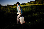 Alexis Koefoed carries fresh water to the chicken houses at Soul Food Farm in Vacaville, CA May 7, 2010.