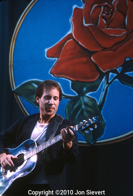 "Paul Simon, Oct 1981, Bread & Rose Festival, Greek Theater. Berkeley. 13-time Grammy Award Winner. American singer-songwriter, known for his success beginning in 1965 as part of the duo Simon & Garfunkel, with musical partner Art Garfunkel. Simon wrote most of the pair's songs, including three that reached number one on the US singles charts, ""The Sounds of Silence"", ""Mrs. Robinson"", and ""Bridge Over Troubled Water"". In 1970, at the height of their popularity, the duo split, and Simon began a successful solo career, recording three highly-acclaimed albums over the next five years. In 1986, he released ""Graceland"", an album inspired by South African township music that helped fuel the anti-apartheid movement"