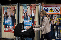 "France. Ile de France. Paris. Partially torn campaign posters of French presidential election candidate Emmanuel Macron for the centrist party ""En Marche"". A mother is pushing her baby stroller near a construction site. 22.04.17 © 2017 Didier Ruef"
