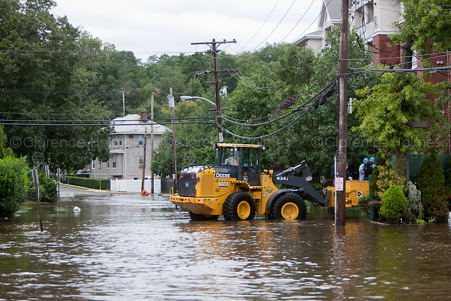 MAMARONECK, NY - AUGUST 28: A Con Edison repair crew works on a transformer on Grand Street from a front loader in the Village of Mamaroneck, New York on Sunday August 28, 2011 in the aftermath of Hurricane Irene.  The crew was working to restore electrical power to the area.