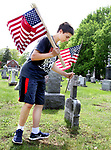 WINSTED CT. 18 May 2018-051818SV03- Caleb Goodell, 14, of Winsted helps his family replace old American Flags with new ones at a cemetery on Oak Street in Winsted Friday. The family replaces the flags at that cemetery every year before Memorial Day.<br /> Steven Valenti Republican-American
