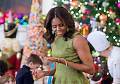 First lady Michelle Obama looks over one of the holiday crafts and treats in the State Dining Room during the preview the 2015 White House Christmas decorations in the East Room of the White House in Washington, DC on Wednesday, December 2, 2015.  She was joined by military families who participated in the making of the crafts.<br /> Credit: Ron Sachs / CNP