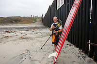 "Tom Jones poses for photographers in front of the US Mexico border at Border Field State Park, the south-western most corner of the contiguous United States, Fiday, November 9 2007.  Jones became the first person to paddle the entire 1250-mile coast of the California on a paddleboard when his three and a half month long journey ended at the border fence in southern San Diego.   The expedition, called ""California Paddle 2007? was designed to draw attention to the problem of plastic pollution in the world?s oceans and its detrimental effect on marine life.  (Photo Ronan Gray)"