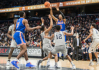 WASHINGTON, DC - DECEMBER 28: Stacy Beckton JR. #2 of American passes the ball over Terrell Allen #12 and Jagan Mosely #4 of Georgetown. during a game between American University and Georgetown University at Capital One Arena on December 28, 2019 in Washington, DC.