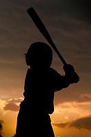 Young boy stands at home plate during practice following a baseball game as the sun set near the end of youth summer baseball season.