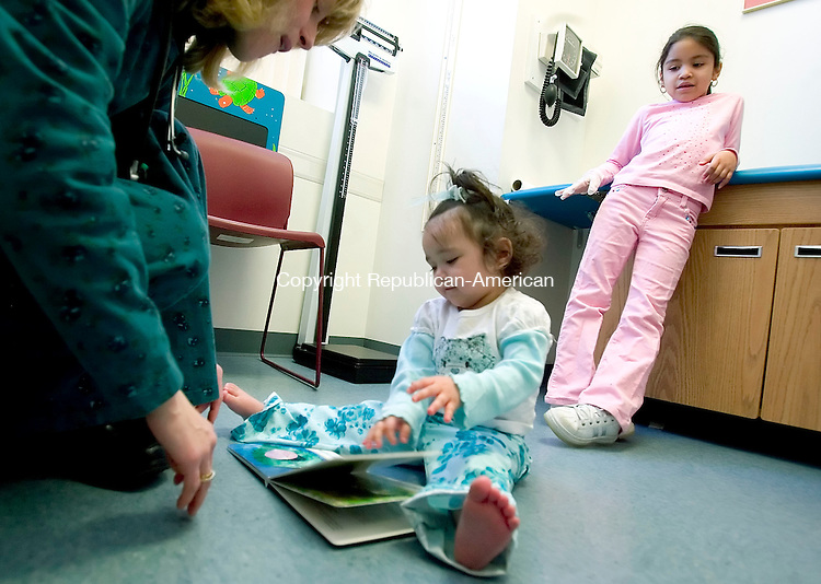 WATERBURY, CT--20 MARCH 2007--032007JS03-Angela Barrows, a Physician's Assistant at The Children's and Family Health Center in Waterbury, left, presents a book to 19-month-old Brenayshalee Malave as her sister Shayralee Santiago, 7, looks on during a visit to the office on Tuesday. Barrows is the program Coordinator for the Reach Out and Read program in the office.<br /> The program provides federal funds to pediatrician's offices with low income patients and allows the doctors to give out a free book to each child when they visit the doctors. <br /> Jim Shannon / Republican-American