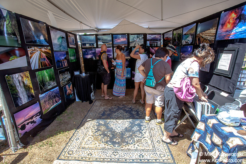 People browsing artwork at Mike Krzywonski Photography's booth at the 16th Annual Haleiwa Arts Festival at Haleiwa Beach Park, North Shore, Oahu, Hawaii
