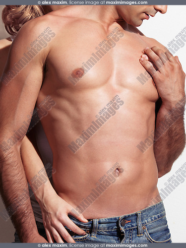 Closeup up of a woman standing behind a man with muscular bare torso. Isolated on white background.
