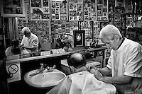 Rome June 19, 2008<br /> The barber shop, the San Lorenzo district, where he works Gaetano and open since 1923 by the father of Gaetano and Gaetano who works there from the age of 11 years. The walls are covered with historic photos of the neighborhood.<br /> Roma 19 Giugno 2008<br /> Il barbiere Gaetano Bordoni e Padre Giustino Ferazzoli. La bottega da barbiere dove lavora Gaetano  e aperta dal 1923 dal padre di Gaetano e Gaetano che ci lavora dall'eta di 11anni. Padre Giustino Ferazzoli figura mitica del calcio laziale, fondatore e anima della AS Basilica San Lorenzo, societ&agrave; nata nello storico quartiere romano.