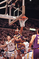 May 13, 1991 - Oakland, USA - Sam Perkins of the Los Angeles Lakers, center, charges through Tom Tolbert (34) of Golden State Warriors and Mitch Richmond, right to score two points during the second half of NBA playoffs at the Oakland Coliseum in Oakland, Ca., Sunday, May 13, 1991.  Perkins scored a total of 27 points to lead the Lakers in a 123-107 victory against the Warriors..(Credit Image: © Alan Greth)