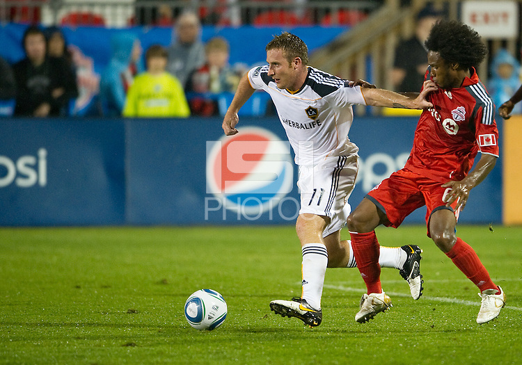 26 June 2010:  Los Angeles Galaxy midfielder Chris Birchall #11 and Toronto FC midfielder Julian de Guzman #6 in action during a game between the Los Angeles Galaxy and the Toronto FC at BMO Field in Toronto..Final score was 0-0...