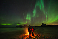 Two people warm themselves by a beach campfire with northern lights - aurora borealis in the sky above, Flakstadøy, Lofoten Islands, Norway
