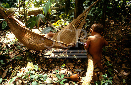 Roraima, Brazil. Yanomami Indian children with a traditional vegetable fibre hammock in the open forest.