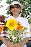 Asian woman holds beautiful bouquet orange tiger lilies and a sunflower. Dragon Festival Lake Phalen Park St Paul Minnesota USA