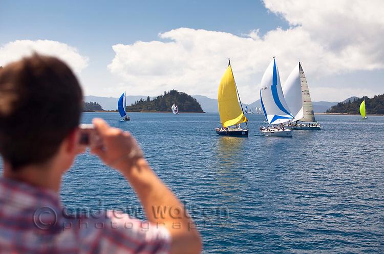 Man photographing yachts racing during Hamilton Island Race Week.  Whitsundays, Queensland, Australia