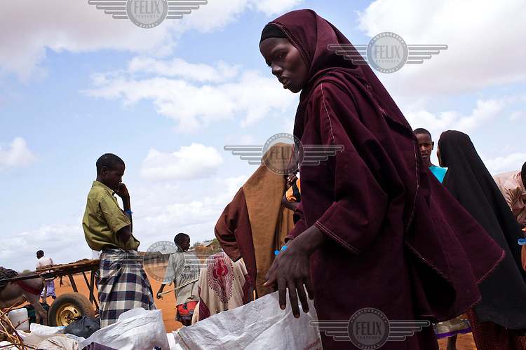 A group of Somali refugees wait outside the registration and food distribution point at the IFO camp, part of the Dadaab refugee camp in Kenya. The drought is the worst in East Africa for 60 years. The UN described it as a humanitarian emergency. The already overcrowded complex received 1,000 new refugees a day in June, five times more than a year ago. About 30,000 people arrived at the Dadaab refugee camp in June, according to UNHCR compared to 6,000 in June 2010.
